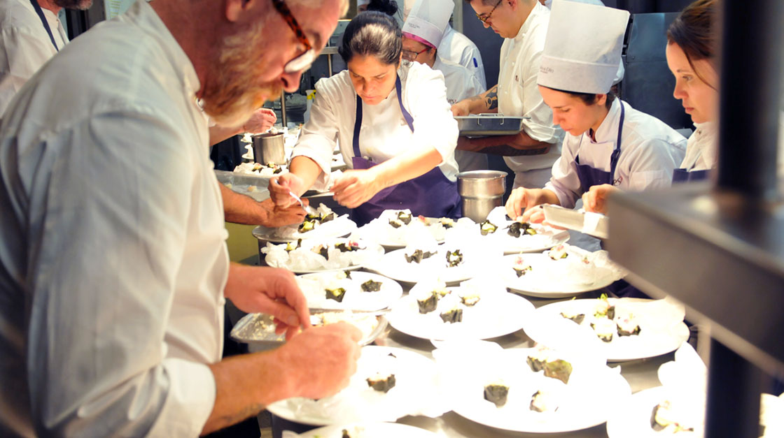 A groups of chefs preparing their own dishes