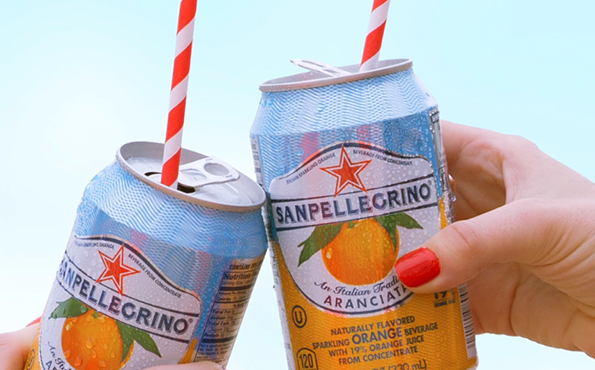 Two cans of Aranciata with drinking straws