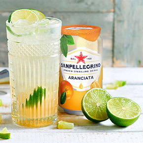 A glass with lime and Sanpellegrino orange flavored drink